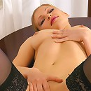 Stockinged lass spreads her buns on top of a table