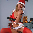 Kitty poses in red stockings and Santa's hat on camera