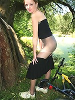 Pantyhosed girl poses right next to her bicycle