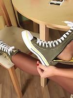 Frisky girl in suntan reinforced toe hose having fun playing with a banana