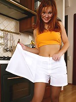 Red-haired girl in control top pantyhose going for foot play in the kitchen