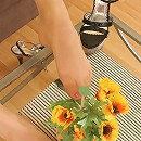 Smashing looking chick touching beautiful flowers with her nyloned feet