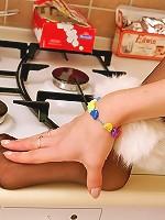 Redhead cutie tenderly massaging her feet in black reinforced toe pantyhose