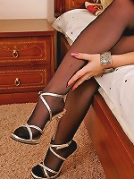 Awesome blonde chick demonstrating her sexy feet in black smooth pantyhose