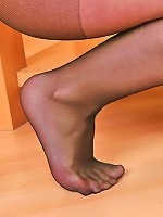Upskirt babe on tiptoe posing her amazing feet encased in black pantyhose
