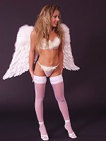 Lustful blonde wearing angel wings and stockings undressing flaunts body